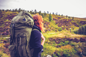 Woman with backpack watching fellow hillwalkers in the distance
