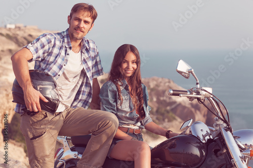 Wall mural Stylish couple on a motorcycle. He put his foot on the exhaust p