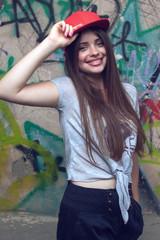 smiling beautiful girl posing near painted  wall.