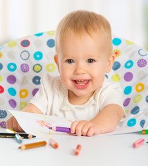 happy baby child draws with colored pencils crayons