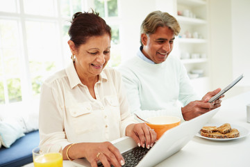 Senior Indian Couple Using Laptop And Digital Tablet At Home