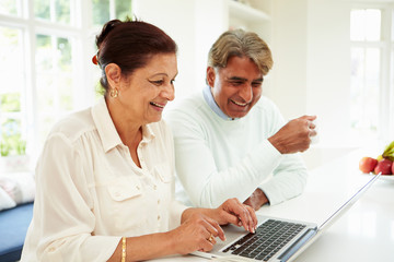 Senior Indian Couple Using Laptop At Home