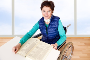 Woman with book sitting in a wheelchair at the table
