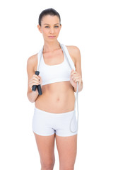 Serious fit sportswoman holding skipping rope around neck