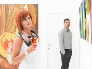 man admiring a beautiful woman at painting exhibition