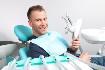 Patient at dentist office. Cheerful young man sitting at the cha