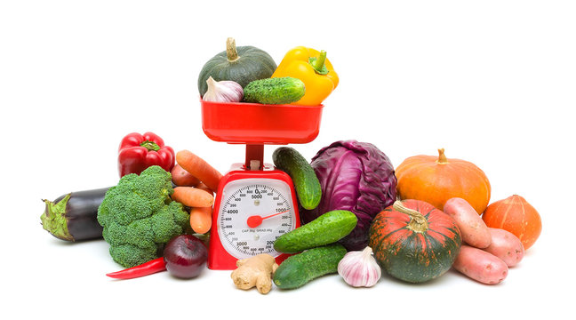 kitchen scale and vegetables isolated on a white background