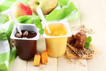 Tasty   cream desserts with pieces of fresh fruits, cookies and