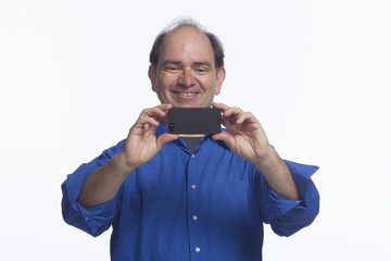 Man smiling and taking picture with his smartphone, horizontal