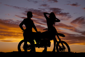 Silhouette of two women by a motorcycle one hands hair