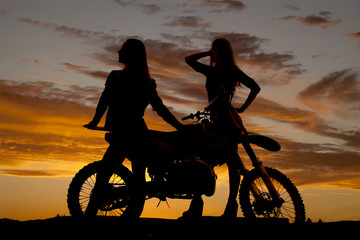 Silhouette two women stand by motorcycle