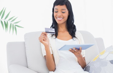 Delighted black haired woman buying online with her tablet pc