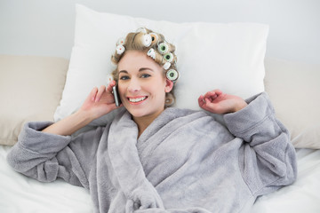 Cute relaxed blonde woman in hair curlers calling with her mobil