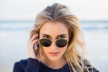 Serious gorgeous blonde on the phone looking over her sunglasses