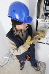 Young man repairing a distribution board