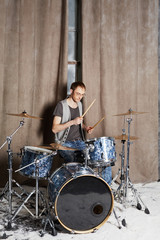 Drummer plays drums in room powdered with snow
