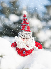 santa toy in snowdrift with snowfall