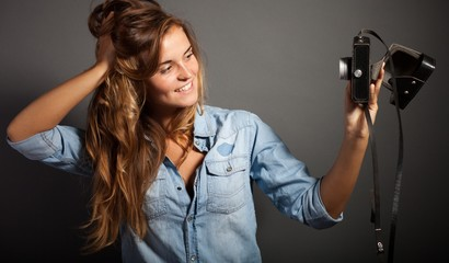 Photographer woman taking pictures herself with old camera
