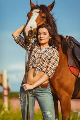 beautiful woman standing near a horse