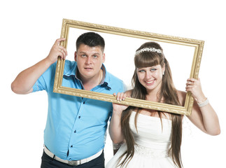 bride and groom are posing with the big frame