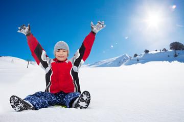 Happy boy sitting on sled on sunny day