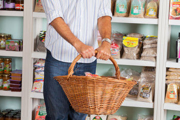 Midsection Of Man Holding Wicker Basket In Store