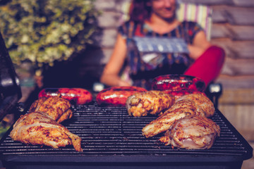 Chicken and sausages on barbecue with woman in background