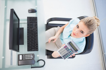 Overhead view of elegant businesswoman showing calculator