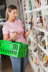 Woman With Shopping Basket Choosing Product