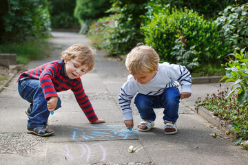 Two little sibling boys painting with chalk outdoors