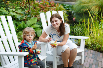 Young woman and little toddler boy eating ice cream outdoors
