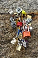 Many love padlocks tied to a wall