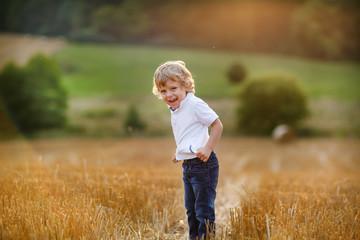 Cute blond little boy having fun on yellow hay field