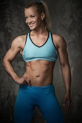 Beautiful smiling muscular bodybuilder woman