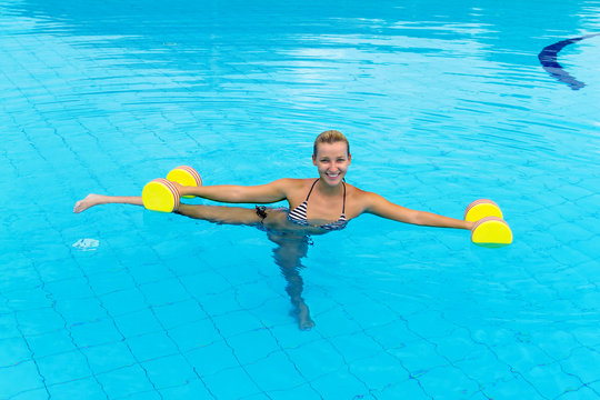 Woman is engaged aqua aerobics in water