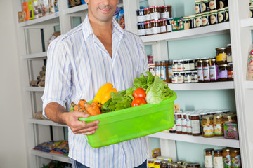 Man With Basket Of Fresh Vegetables Standing In Store