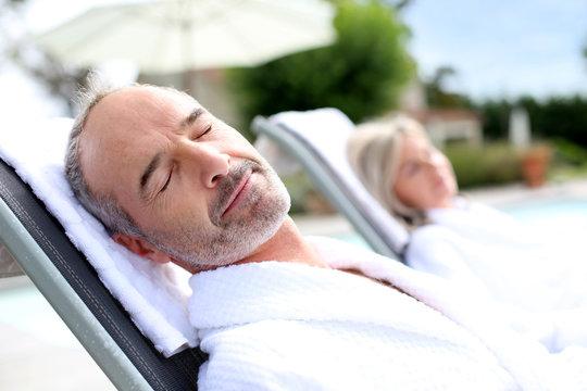Senior man in spa hotel relaxing in long chair