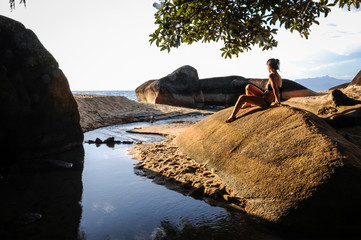 Model enjoying the sunset of the tropical island at Ilha Grande,