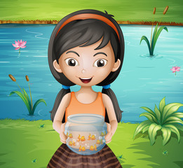 A smiling young girl holding an aquarium