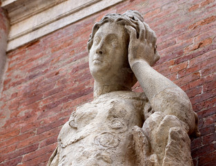 statue with headaches with red brick background