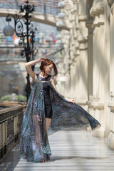 Happy young woman in a fashionable flutter transparent cape
