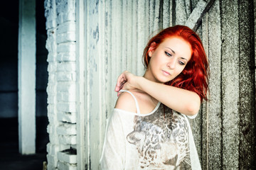 beautiful girl with red hair outdoor against wooden doors