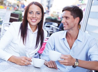 Young couple with cups sitting in a summer cafe