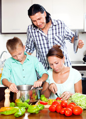 Happy family cooking vegetarian lunch