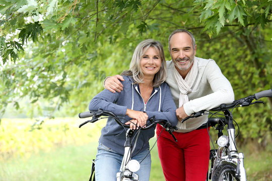 Cheerful senior couple with bicycle in country path