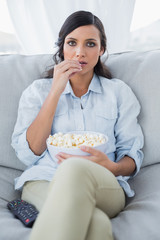 Concentrated pretty brunette watching tv and eating pop corn