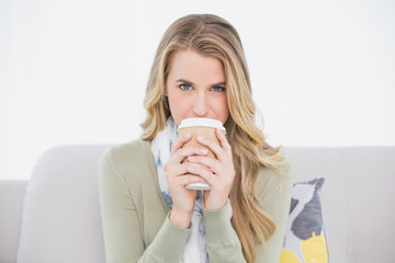 Cheerful cute blonde drinking coffee sitting on cosy sofa