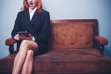 Businesswoman on sofa reading exciting things on tablet
