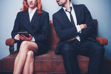 Sloppy businessman spying on successful female coworker