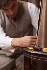 Tailor at work. Confident young tailor sewing clothes at tailor